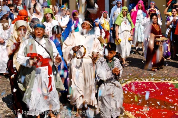 Merrymakers dance and play music while paper confetti rains down from rooftops over the procession, Antigua, Guatemala