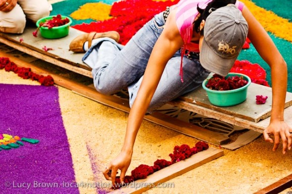 Lying on raised wooden planks to decorate and avoid damaging alfombras, Antigua, Guatemala