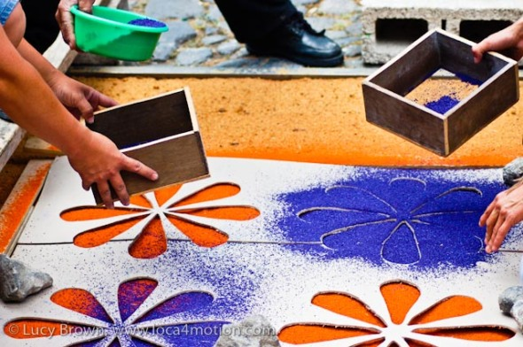 Sifting blue sawdust (aserrín) flowers on to the orange base using a cardboard stencil, Antigua, Guatemala