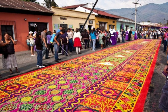 Spraying a completed sawdust alfombra with water to stop it drying and blowing away in the wind, Antigua, Guatemala