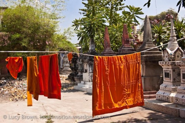 Monks' robes drying in the sun among tombs, Wat Sidamduan, Vientiane, laos