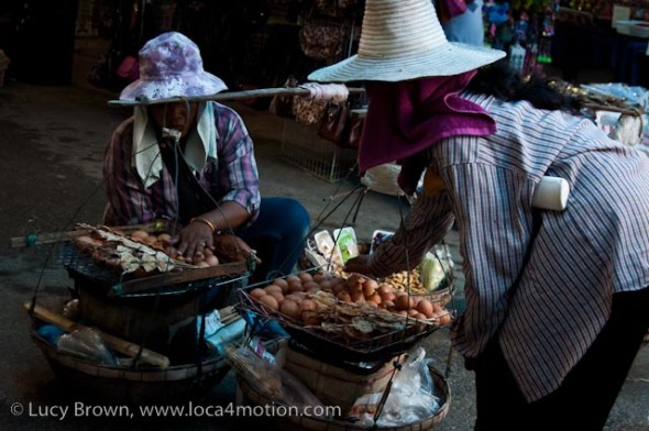 Vendors selling eggs cooked on portable charcoal grill, dried squid on sticks, peanuts and fruit, street food, Thailand