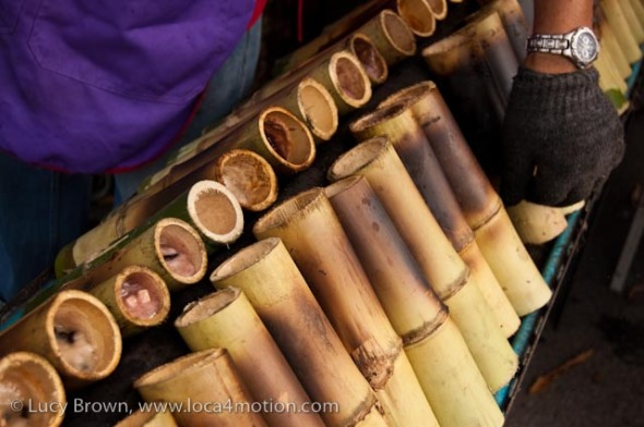 Pieces of bamboo filled with khao lam (a mixture of sticky rice, coconut milk, black beans and taro root) cooking over charcoal at a street stall, desserts, Thailand
