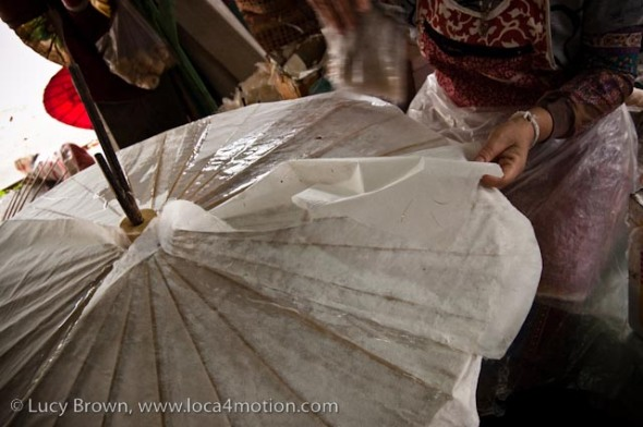 Glueing layers of sa paper to parasol frame, traditional Thai parasols, Chiang Mai, Thailand