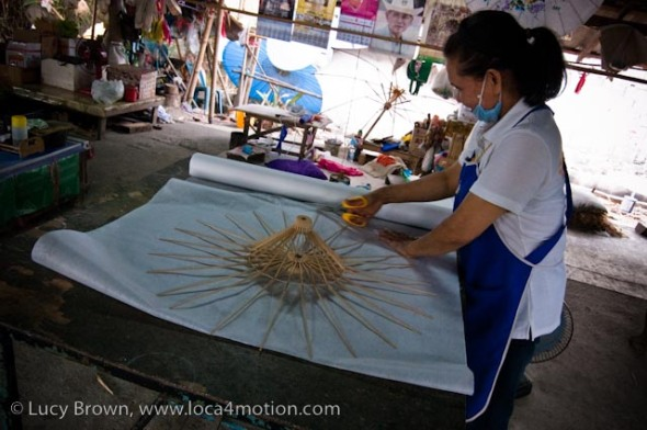 Cutting sa paper to size around a parasol frame, traditional Thai parasols, Chiang Mai, Thailand