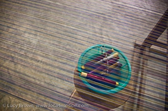 Spindles of Thai silk thread seen through threads on loom, Chiang Mai, Thailand
