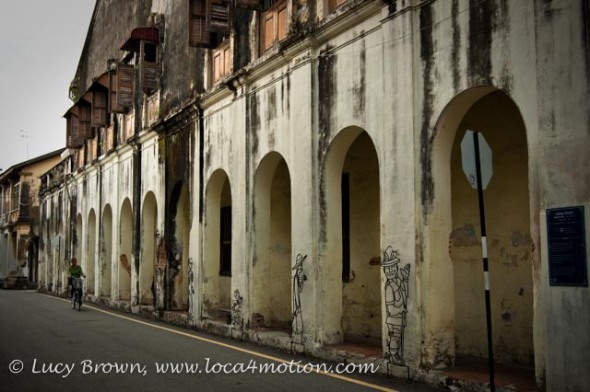 Cycling past old building and metal street art, George Town, Penang, Malaysia