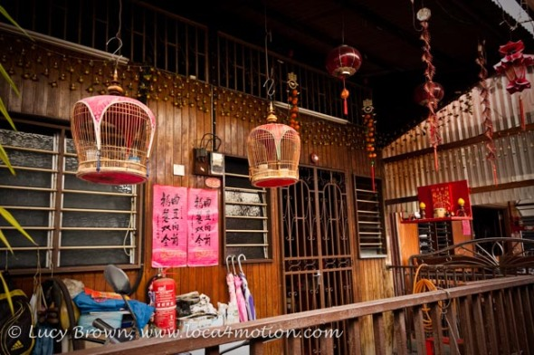Jetty home with hanging bird cages and Chinese shrine, Chew Jetty, Clan Jetties, George Town, Penang, Malaysia