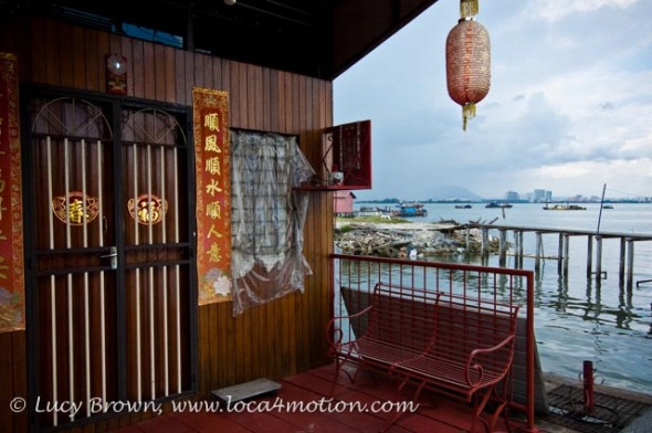 Jetty home with hanging Chinese lantern and view of water, boats and city skyline, Lee Jetty, Clan Jetties, George Town, Penang, Malaysia