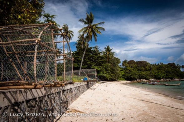 Fish traps by the beach & long tail boats moored offshore at the Sea Gypsy village, Rawai, Phuket, Thailand