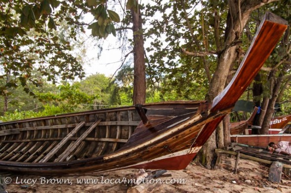 Beached long-tail boats & sleeping fisherman near the Sea Gypsy village, Rawai, Phuket, Thailand