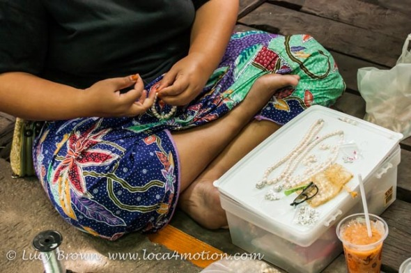 Woman threading strings of locally farmed pearls to sell, Koh Panyee (Ko Panyi), Phang Nga Bay, Thailand