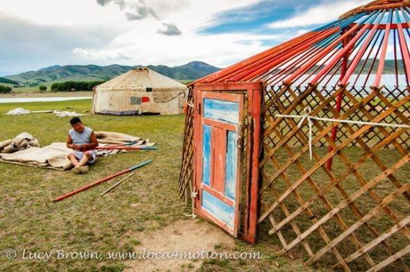Contructing a Mongolian ger. Wooden wall lattice, roof poles and door. Khutag Ondor, Central Mongolia